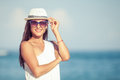 Fashion lifestyle beautiful girl on the beach at in sunglasses and white hat day time travel and vacation Royalty Free Stock Images
