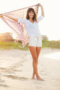 Fashion lifestyle beautiful young woman on the beach at sunset warm backlit sunlight Stock Image