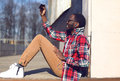 Fashion lifestyle photo happy young african man makes selfie self portrait on the smartphone outdoors hipster wearing a red plaid Stock Photography