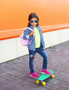Fashion little girl child with skateboard wearing a sunglasses and checkered shirt and backpack over orange Royalty Free Stock Photo