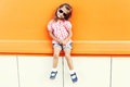 Fashion little girl child wearing a sunglasses and checkered shirt in city over colorful background