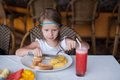 Fashion little girl having breakfast at resort adorable restaurant Royalty Free Stock Photos
