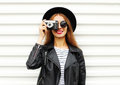 Fashion look, pretty cool young woman model with retro film camera wearing elegant hat, leather rock jacket over white Royalty Free Stock Photo