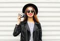 Fashion look, pretty young woman model with retro film camera wearing elegant black hat, leather rock jacket over white Royalty Free Stock Photo