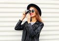 Fashion look, pretty young woman model with retro film camera wearing elegant hat, leather rock jacket over white Royalty Free Stock Photo