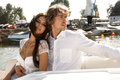 Fashion lovely beautiful couple posing on the luxury boat in open sea in summer young men and sensual brunette outdoor portrait in Royalty Free Stock Photos