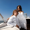 Fashion lovely beautiful couple posing on the luxury boat in open sea in summer young men and sensual brunette outdoor portrait in Stock Images