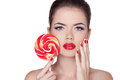 Fashion make up beauty girl portrait holding colorful lollipop hot red lips nail polish manicured nails skin care isolated on Royalty Free Stock Photography