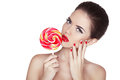 Fashion makeup beauty girl portrait holding colorful lollipop hot red lips nail polish manicured nails skin care isolated on white Royalty Free Stock Images