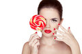 Fashion makeup beauty girl portrait holding colorful lollipop hot red lips nail polish manicured nails skin care isolated on white Stock Images
