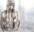 Fashion male portrait of a beautiful model in fur hat and vest against modern background with copy space Royalty Free Stock Photo