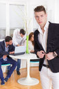 Fashion man in a business atmosphere with colleagues behind him young modern men Royalty Free Stock Photo