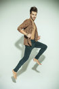 Fashion man jumping against grey background pulling his jacket while looking at you Royalty Free Stock Photography