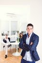 Fashion man standing in business atmosphere with colleagues in b men sulking behind him working as team Stock Images