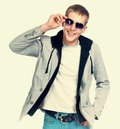 Fashion man in sunglasses smiling on light background Stock Images