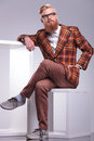 Fashion man in vintage clothes and long beard seated looking away to his side studio shot Royalty Free Stock Photography