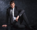 Fashion model in black suit and tie is resting attractive young on studio floor Stock Photos