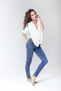 Fashion model in a blouse and jeans barefoot