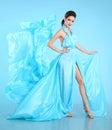 Fashion model in blue blowing chiffon dress. Glamour stunning Woman in long flying silk fabric waving on wind evening dress. Royalty Free Stock Photo