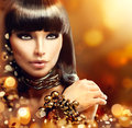 Fashion model brunette girl with golden accessories Stock Photography