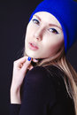 Fashion model with creative blue make up and blue nails in blue portrait of hat isolated on black background Stock Photo