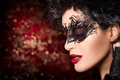 Fashion model girl face in creative artistic masquerade makeup with with dramatic black twirls and tendrils gorgeous dark haired Royalty Free Stock Photo