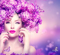 Fashion model girl with lilac flowers hairstyle