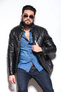 Fashion model in leather jacket and sunglasses posing for the camera studio Stock Image