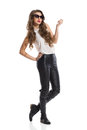 Fashion model in leather trousers fashionable woman with curly hair posing sunglasses black boots and white shirt full length Royalty Free Stock Image