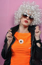 Fashion model in orange blouse and white wigs with sunglasses posing studio Stock Image