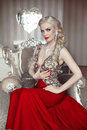 Fashion model portrait of beautiful sensual blond woman with makeup in luxurious dress with bijou, posing on modern armchair with Royalty Free Stock Photo