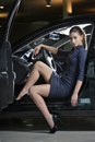 Fashion model posing in a car gorgeous female driver wearing fashionable dark blue dress and black high heel shoes is sitting Royalty Free Stock Photo