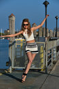 Fashion model posing pretty on the pier in sunny weather wearing white top, sailor shorts and sunglasses. Royalty Free Stock Photo