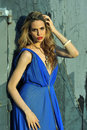 Fashion model posing sexy wearing long blue evening dress on rooftop location Stock Photo