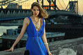 Fashion model posing sexy wearing long blue evening dress on rooftop location with metal bridge construction background Royalty Free Stock Image
