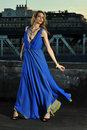 Fashion model posing sexy wearing long blue evening dress on rooftop location with metal bridge construction background Stock Photography