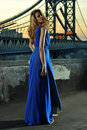 Fashion model posing sexy wearing long blue evening dress on rooftop location with metal bridge construction background Royalty Free Stock Photography