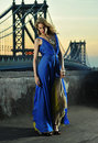 Fashion model posing sexy wearing long blue evening dress on rooftop location with metal bridge construction background Stock Photo