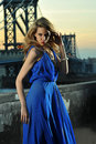 Fashion model posing sexy wearing long blue evening dress on rooftop location with metal bridge construction background Stock Image