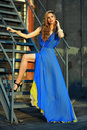 Fashion model posing sexy wearing long blue evening dress on rooftop location with metal stairs background Stock Photography