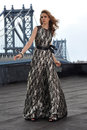 Fashion model posing sexy wearing long evening dress on rooftop location with metal bridge construction background Royalty Free Stock Photography
