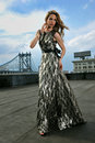 Fashion model posing sexy wearing long evening dress on rooftop location with metal bridge construction background Stock Images
