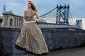 Fashion model posing sexy wearing long evening dress on rooftop location with metal bridge construction background Royalty Free Stock Images