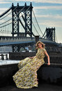 Fashion model posing sexy wearing long evening dress on rooftop location with metal bridge construction background Stock Photography