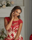 Fashion model in red dress beautiful young tan wearing and white posing luxury home scene Stock Image