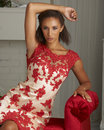 Fashion model in red dress beautiful young tan wearing and white posing luxury home scene Stock Photography