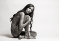 Fashion model sitting on a floor in a jeans barefoot on a white Royalty Free Stock Photo
