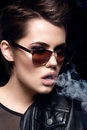 Fashion model smoking cigarette wearing sunglasses. Sexy woman portrait over dark background. Attractive fashion girl posing. Royalty Free Stock Photo