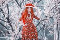 Fashion model in spring flower garden. Valentine day background. Retro dress. Awesome redhead lady in dress. Woman in awesome Royalty Free Stock Photo