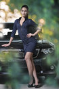 Fashion model standing next to fancy car blurred green color bubbles background beauty female wearing stylish dark blue dress and Royalty Free Stock Photos